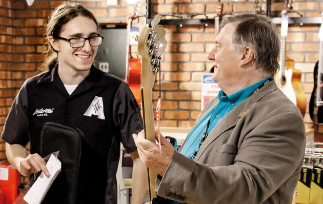 Staff member with customer holding guitar