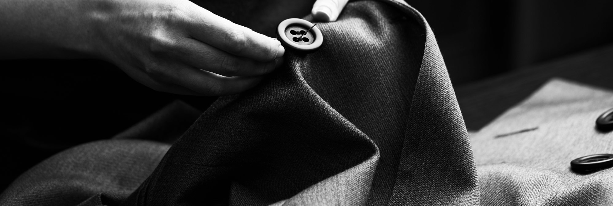 Close-up of hand carefully sowing a button on to a jacket