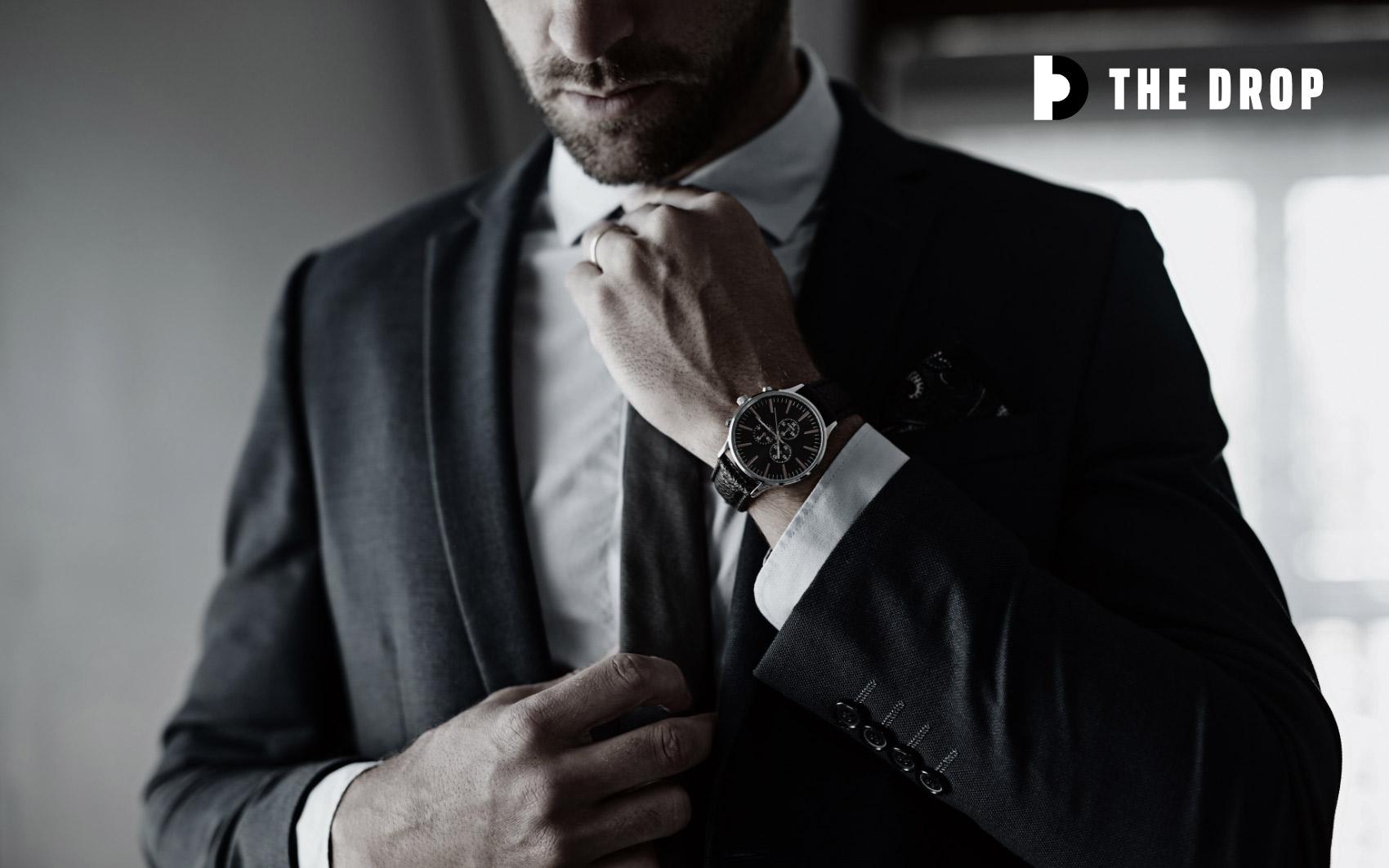 Man in suit adjusting tie with logo