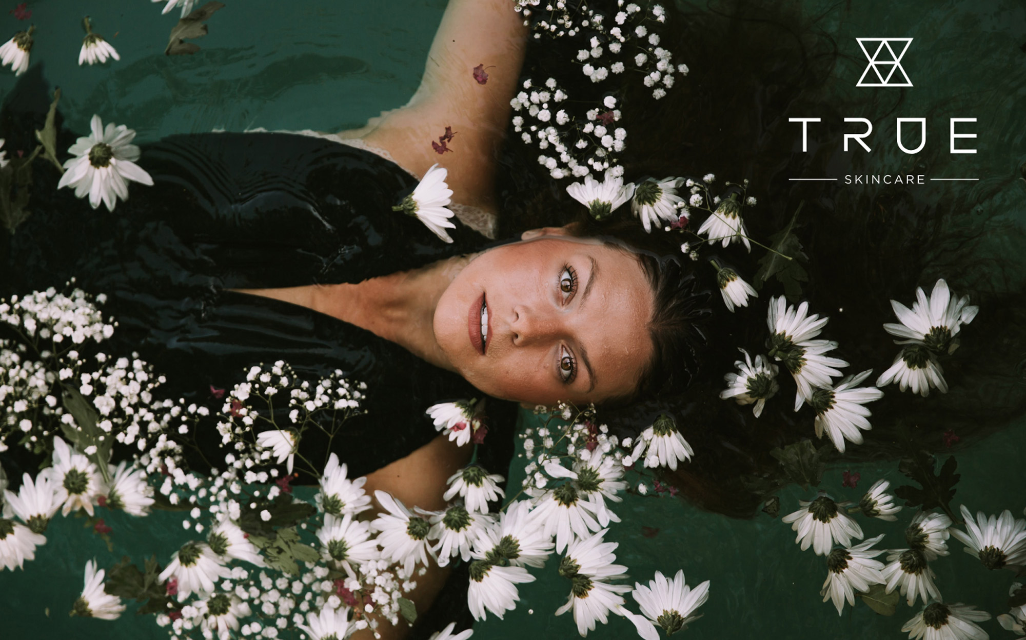 Woman laying in water surrounded by flowers