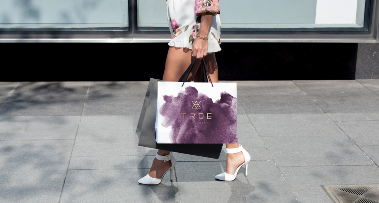 woman walking along sidewalk with Ture Skincare bag